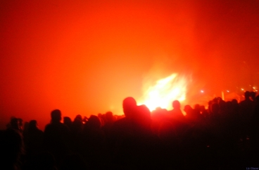 the bonfire, in full commanding roar, seems to cast a spell of silent awe upon the watching crowds