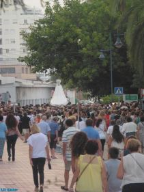 The procession makes its way past the fishermen's warehouses towards El Cable beach