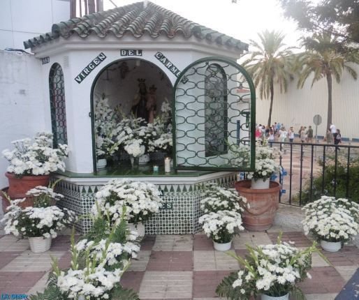 A shrine to the Virgen del Carmen adorned with white flowers in the fishermen's quarter