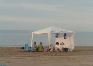 """Falling on a Sunday, some local people had already """"set up shop"""" for a family day on the the beach."""
