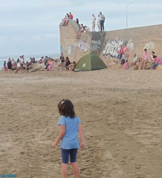 People watch from the fishing port walls as children play in the sand
