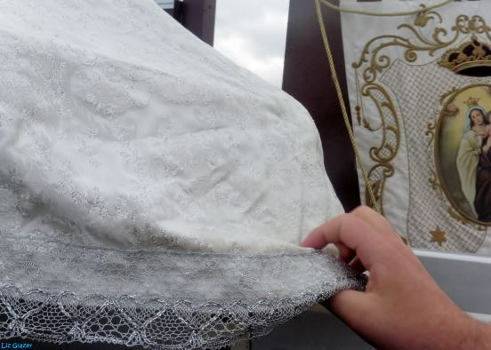 The Virgen del Carmen is returned to the altar while the people file past, touching the hem of her gown for blessings and protection