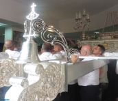The male throne-bearers, gathered between the much heavier silver throne that will carry the Virgen del Carmen on a boat in the sea procession that evening, look on (with trepidation?) while the women lower the throne at its resting place.